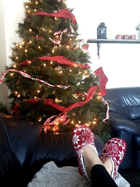 Sitting by the Christmas tree with red slippers